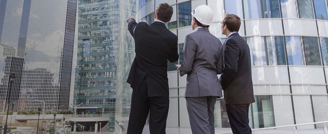 three men in suits looking at buildings